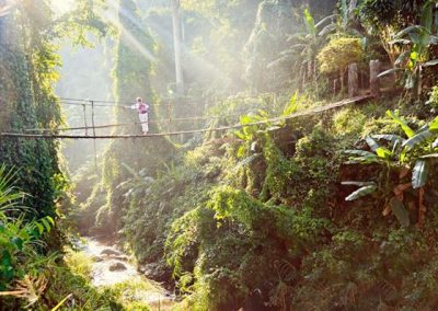 woman-crossing-suspension-bridge-in-thailand-rainforest